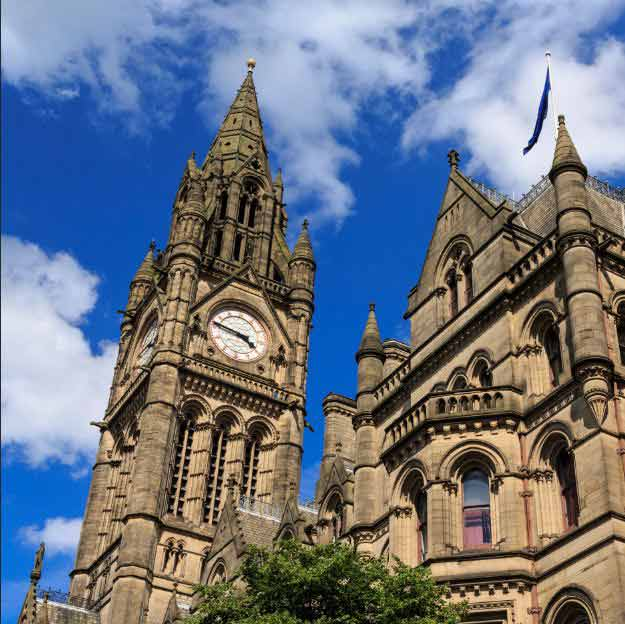 a photograph taken looking up at the clock tower of Manchester Town Hall